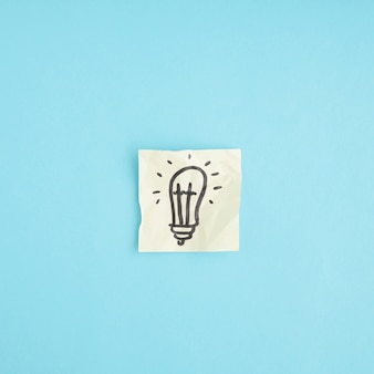 Hand drawn light bulb on the crumpled paper against the blue background