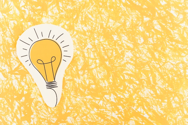 Hand drawn light bulb cut out over the yellow pattern background