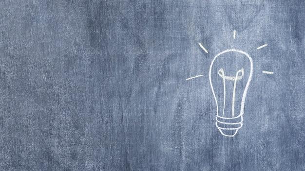 Hand drawn light bulb drawn with chalk on chalkboard