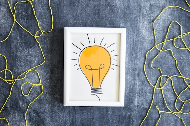 Hand drawn light bulb frame with yellow wool thread on chalkboard
