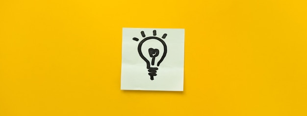 Hand drawn light bulb icon on sticky note paper