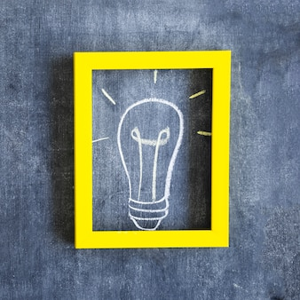 Hand drawn light bulb inside the frame with yellow border on chalkboard