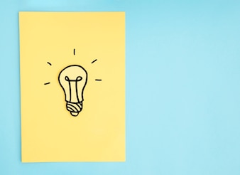 Hand drawn light bulb on yellow paper over the blue background
