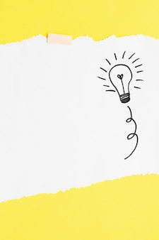 Hand drawn light bulb on white card paper over yellow backdrop