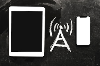 Hand drawn network signal icon between the digital tablet and cellphone on chalkboard