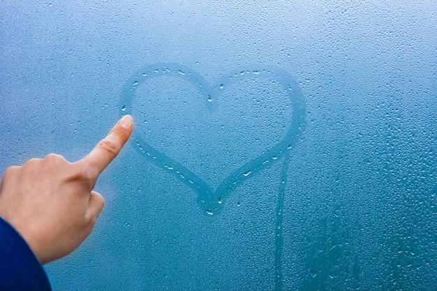 손 방울 배경으로 유리창에 마음을 그립니다