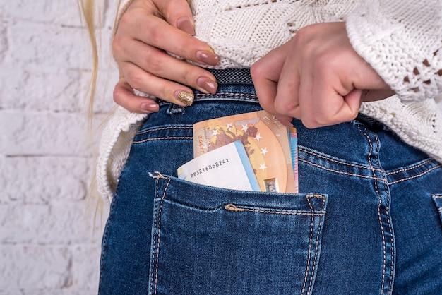 Рука вынимает банкноты евро из кармана джинсов