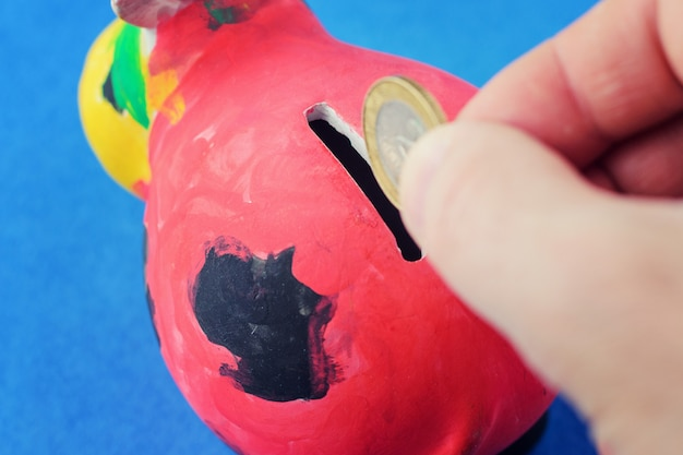 The hand drops the coin into the coin box. red piggy bank, paint