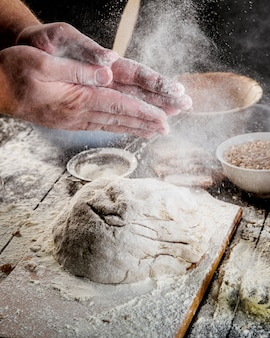 Hand dusting with flour on dough over the table