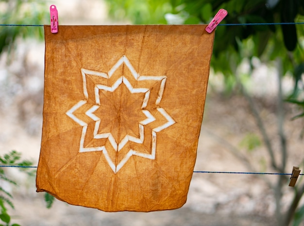 Hand-dyed batik cloth hanging in the outdoor garden.