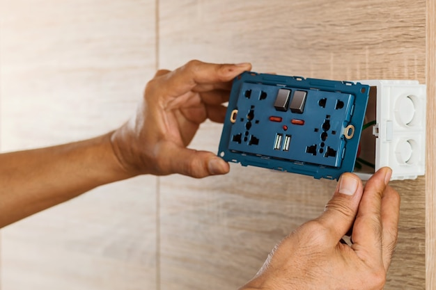 Hand of an electrician are installing the universal wall outlet ac power plug with usb port and on-off in a plastic box on a wooden wall.