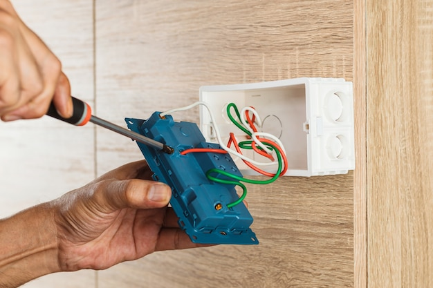 Hand of an electrician is using a screwdriver to attach the wires to the socket.