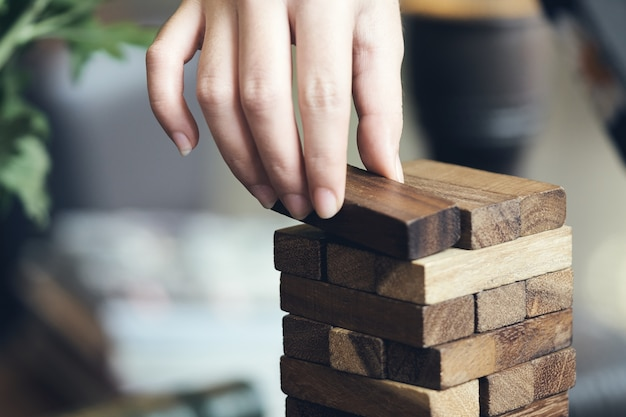 Hand of engineer playing a blocks wood game