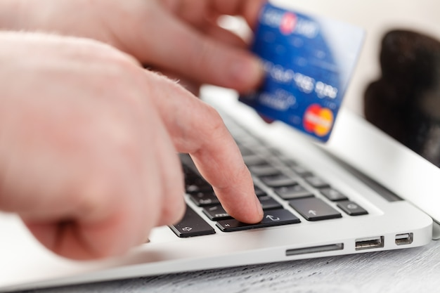Hand entering data using laptop while holding a credit card in the other hand