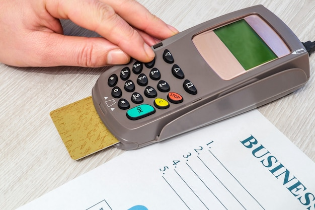Hand entering pin code to money terminal before payment on office desk