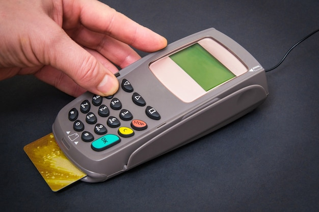 Hand entering pin code to money terminal before payment