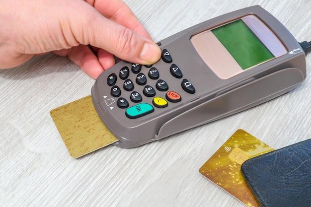 Рука, вводящая пин-код в денежный терминал перед оплатой на офисном столе