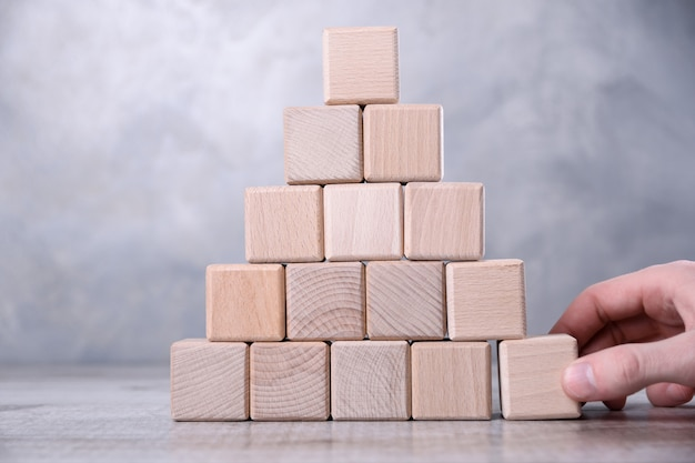 Hand extracts blank wooden cube with space for your word, letter, symbol on the table. one person's influence on the team.place for text, free copy space