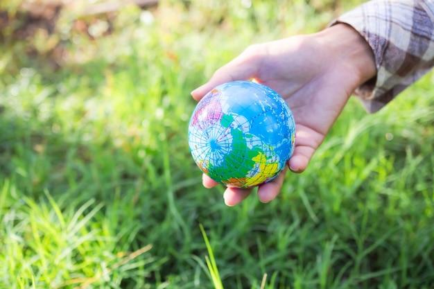 잔디 배경에 지구를 들고 손 농부입니다. 환경 보호 지구의 날, 보존, 숲의 날, 세계 지구 개념을 위한 카드.