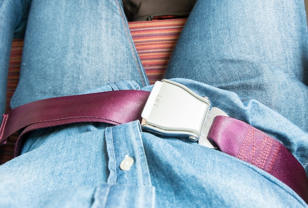 Hand fasten seat belt at seat on airplane before take off
