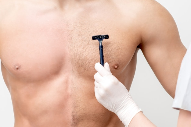 Hand of female beautician shaves chest of young man by razor. concept of hair removal