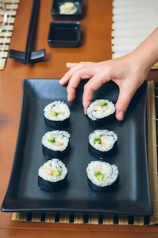 Hand of female chef placing japanese sushi rolls with rice, avocado and prawns on nori seaweed sheet over a black rectangular tray