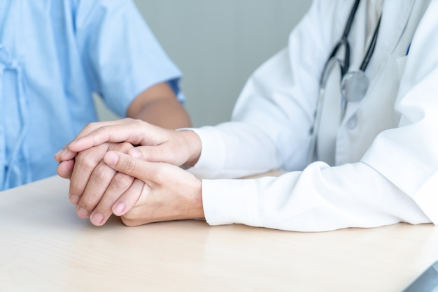 Hand of female doctor holding on her senior patient