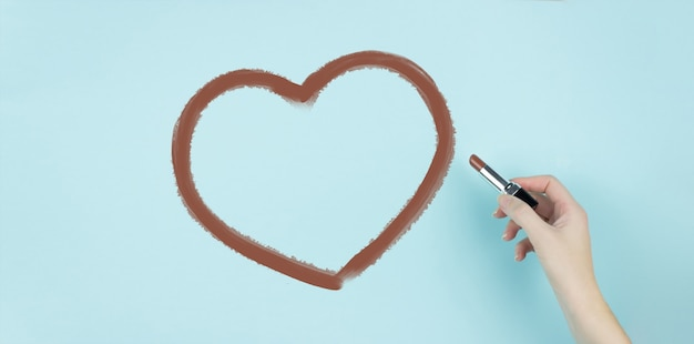 Hand of female draw heart with brown lipstick on blue background.