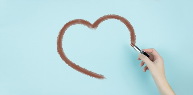 Hand of female draw part of heart with brown lipstick on blue background.