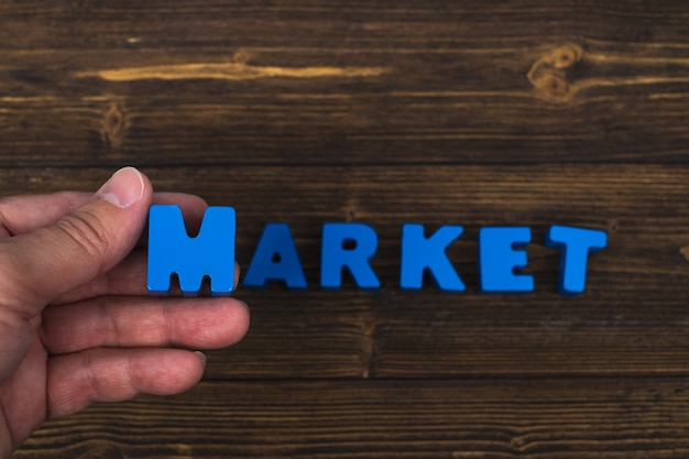 Hand and finger arrange text letters of market word on wood table, with copy space for add advertising word or product.