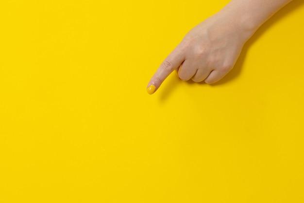 黄色の背景、クローズアップの何かを指している手の指。てぶり。バナー。