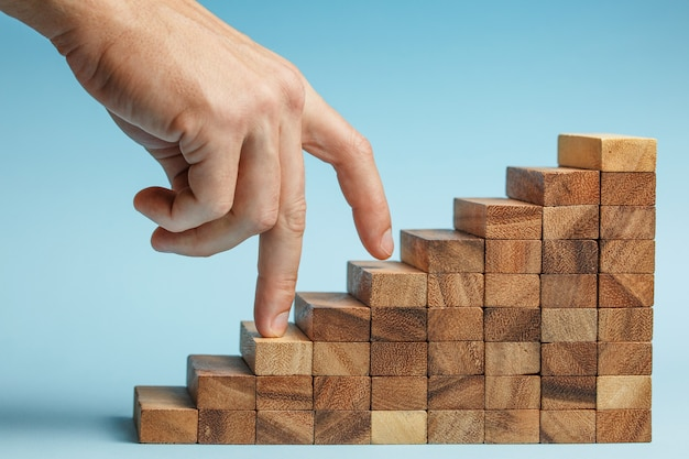 Hand finger walk on stacked wooden block like stairs. rises on the steps. business development and growth concept.