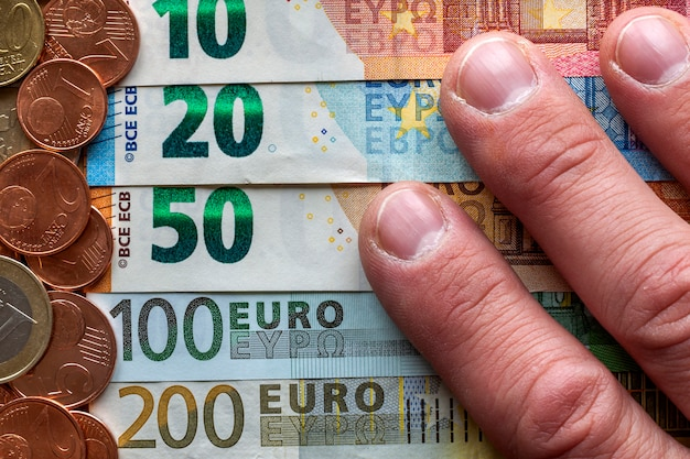 Hand fingers on background of neatly arranged stack of euro banknotes, currency bills worth ten, twenty, one and two hundred euro and different metal coins. money, busyness and finances.