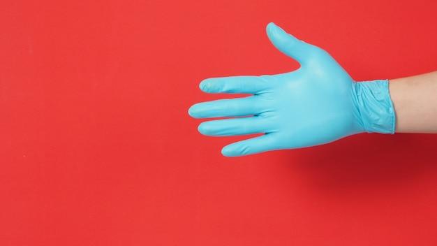 赤い背景に天然ラテックス手袋または外科用手袋を手でフィットさせます。