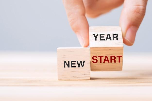 Вручите перевернуть деревянный блок с новым годом, чтобы начать новый текст на фоне таблицы. решение, стратегия, решение, цель, бизнес и праздничные концепции