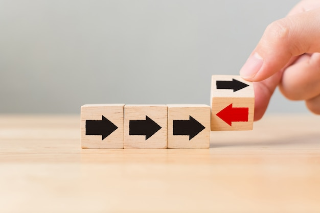 Hand flip over wooden cube block with red arrow facing the opposite direction black arrows, unique, think different, individual and standing out from the crowd concept