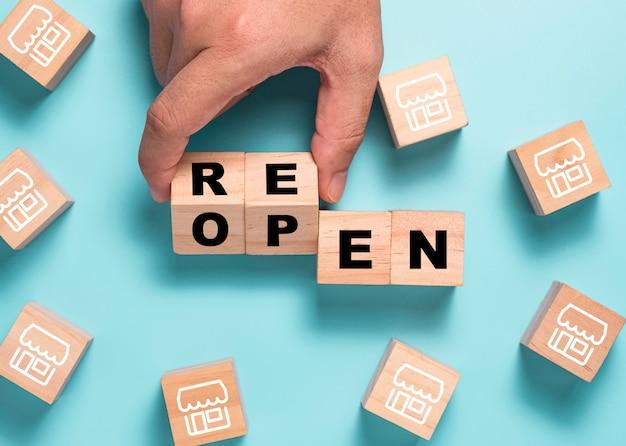 Рука, переворачивающая вновь открывающийся разделительный экран на деревянном кубическом блоке среди магазина иллюстраций. торговый центр и рестораны снова открываются после covid 19.