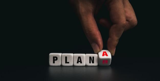 흰색 주사위 블록을 계획 a로 뒤집는 손을 어두운 배경에서 백업 계획 b로 변경합니다. 문제 해결, 전략, 분석, 마케팅의 개념.