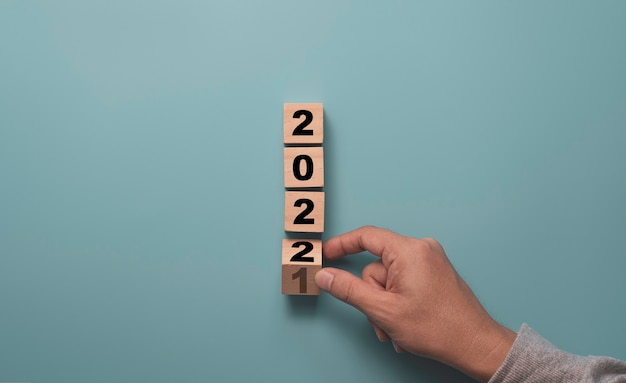 Hand flipping wooden block cube to change 2021 to 2022 on blue background, merry christmas and happy new year preparation concept.