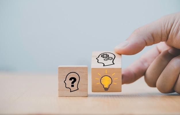 木製のブロックキューブを手で弾くと、人間の質問から賢い思考と解決策の問題に変わります。それは創造的思考のアイデアとイノベーションのコンセプトです。
