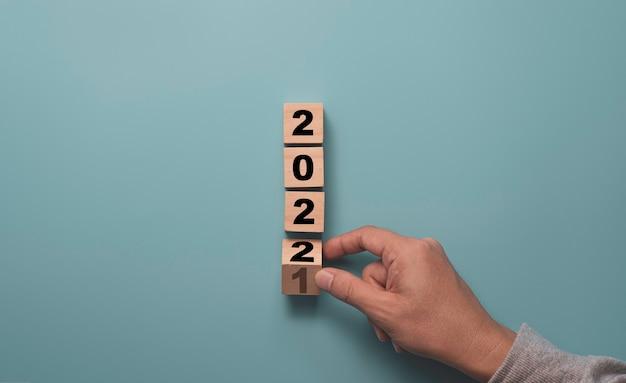 파란색 배경, 메리 크리스마스, 해피 뉴가 어 준비 개념에 2021을 2022로 변경하려면 나무 블록 큐브를 뒤집는 손.