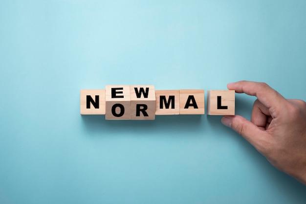 새로운 일반 문구에 대 한 나무 블록 큐브를 내리고 손. 세계는 새로운 표준 포함 비즈니스로 균형을 변경