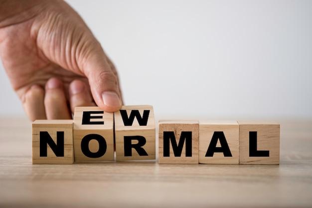 Рука переворачивает деревянные кубики для новой нормальной формулировки.