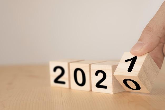 Рука переворачивает деревянные блоки на период с 2020 по 2021 год. новый год и концепция праздника.