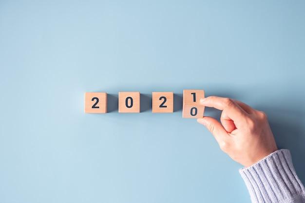 Рука переворачивает деревянные блоки для изменения с 2020 по 2021 год на синем бумажном фоне.