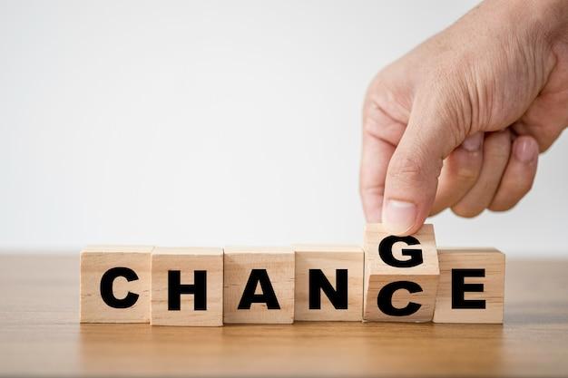 「チャンス」から「チャンス」への言い回しのための木製の立方体のブロックをひっくり返す手。経済投資ビジネスの危機とテクノロジーの変革は、大きなチャンスをもたらします。