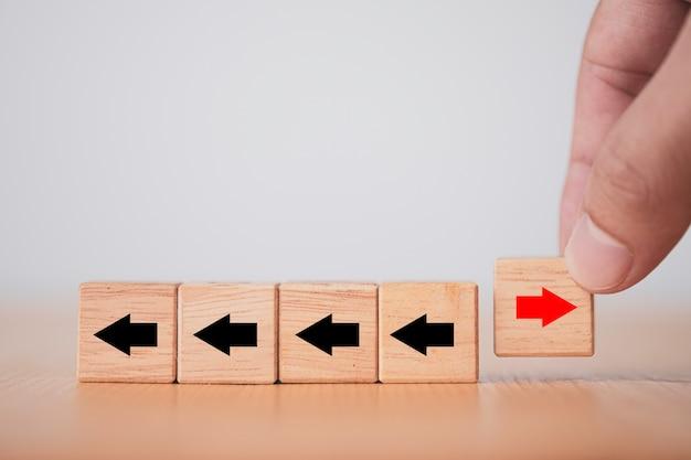 ビジネスの混乱とさまざまな考え方のために、木製の立方体ブロックの赤い矢印を左から右に手で反転させます。