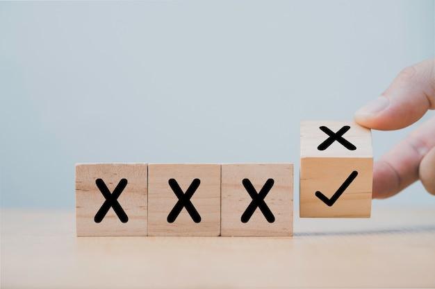 Рука переворачивает деревянный кубический блок, чтобы изменить неправильный крест на правильную отметку.