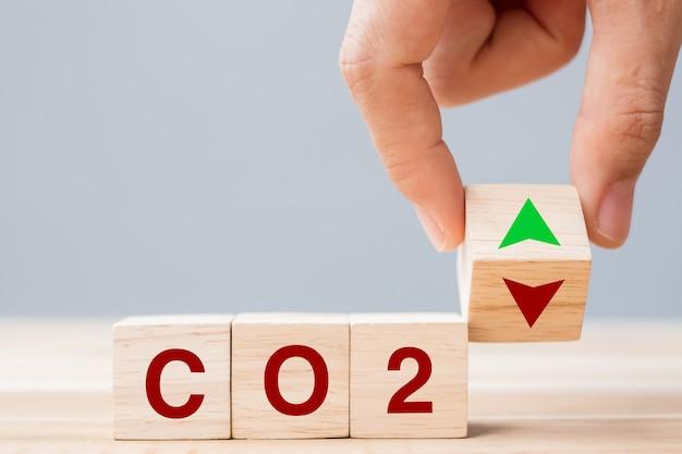 테이블 배경에 co2(이산화탄소) 텍스트가 있는 위쪽 및 아래쪽 화살표 기호로 나무 큐브 블록을 손으로 뒤집습니다. 자유 탄소, 대체 에너지 및 글로벌 기후 변화 개념