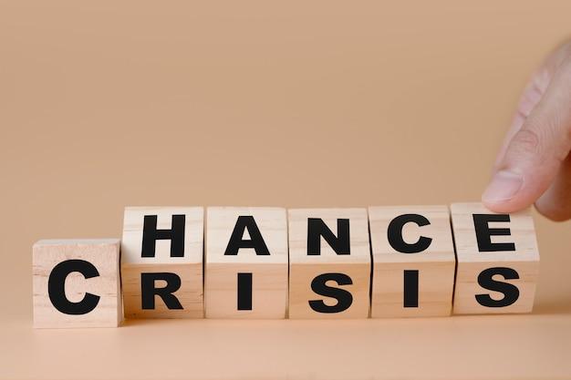 「クライシス」から「チャンス」への変化の表現のために木製の立方体を手でめくる。マインドセットは人間の発達にとって重要です。